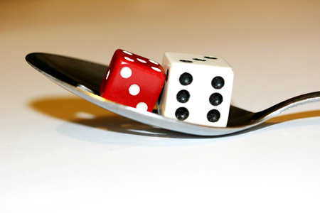 Eating good or bad luck dices on a spoon conceptual image close up