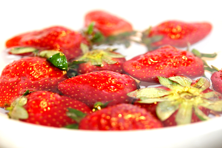 Strawberries floating submerged in clean water on white photo