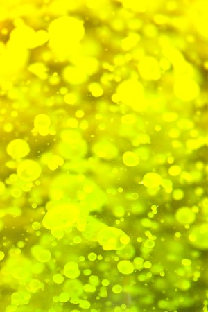 Yellow and green brilliant paint drops mixing liquid abstract background photo