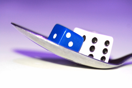 playing with spoon: Two dices on a spoon closeup on blue, food conceptual stock image Stock Photo