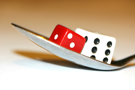 double the chances: Food surprises as a game with gmo conceptual image of dices on a spoon Stock Photo