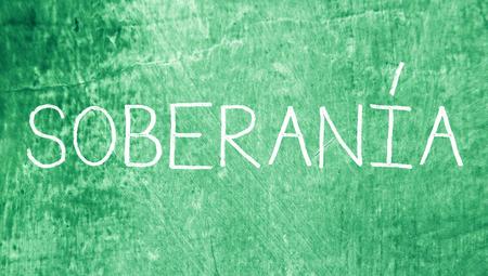 sovereignty: Sovereignty spanish handwritten chalk word on green grunge background