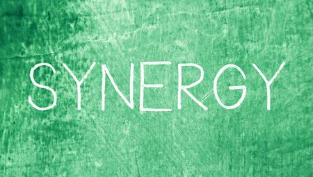 sinergia: Sinergia tapas palabra de tiza sobre fondo verde sucio