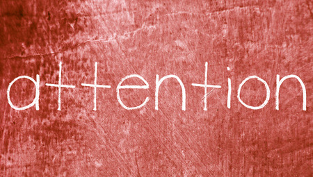 redish: Attention english word on vintage red background Stock Photo