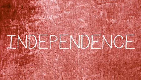 redish: Independence concept chalk word on red grungy background