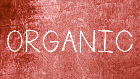 organic concept: Organic concept caps word on red grunge background Stock Photo