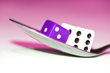 double the chances: Fortune game with food of dices on a spoon on purple conceptual image Stock Photo