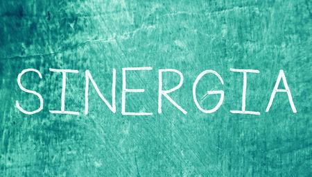 sinergia: Sinergia palabra de letras de tiza sobre fondo azul del grunge Foto de archivo