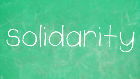 solidaridad: Solidaridad tiza palabra en el fondo de color verde pizarra