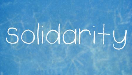 solidaridad: Solidaridad palabra escrita a mano en la pizarra azul