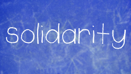 solidaridad: palabra solidaridad escrito con tiza en azul