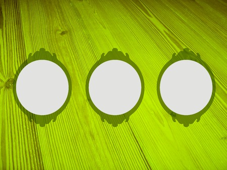 greenish blue: Three empty circular frames on luminous green vintage wood background