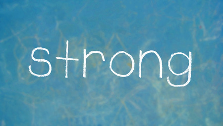 strong: Strong chalk letters word on blue Stock Photo