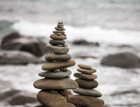 Pebbles on the sea coast. Little cairn on the background of the sea. Landscape for meditation.
