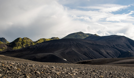 Dramatic iceland landscape with a green hill and black lava looks like a moon