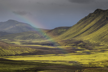 Dramatic iceland landscape with a green hill and black lava looks like a moon. Serenity of Iceland.