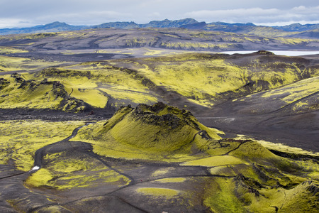 Dramatic iceland landscape of Craters of Laki volcanic fissure with a green hill and black lava looks like a moon. 스톡 콘텐츠