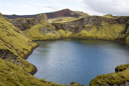 Dramatic iceland landscape with a green hill and black lava and and blue mirror mountain lake. Iceland