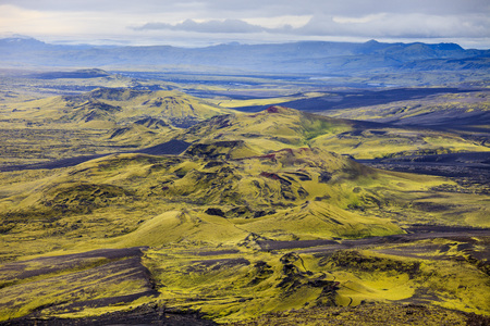 Dramatic iceland landscape of Craters of Laki volcanic fissure with a green hill and black lava looks like a moon 写真素材