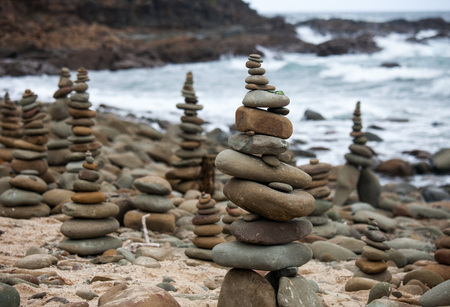 Pyramids from pebble on the sea coast. Little cairns on the background of the sea. Landscape for meditation.