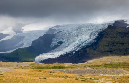 Tongue of Glacier in Iceland drifting down from the green moss mountain in the foggy day. Blue glacier ice is visible, as well as green moss covering rocks of the mountain