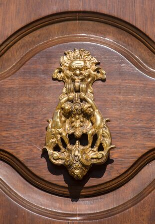 An old style decorative bronze door handle on a wooden door, the distinctive feature and symbol of Malta in Mdina.