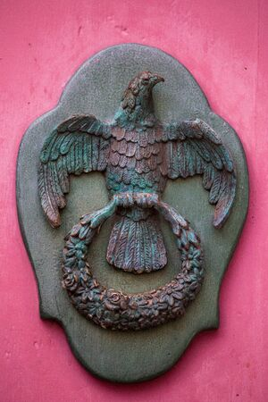 An old style decorative bronze door handle on a wooden door, the distinctive feature and symbol of Malta in Mdina