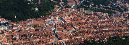 Aerial view and panorame of the Old Town, Brasov with an old clock tower in the middle of square and o lot of red roofs. Transylvania, Romania.