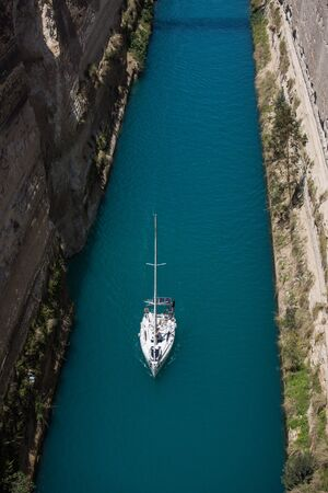 Aerial bird's eye view photo taken by drone of famous Corinth Canal with turquoise water and lonely white yacht , Peloponnese, Greece. The narrowest channel in the world and engineering marvel