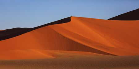 Beautiful landscape with red huge sand dunes at sunset in desert. Sossusvlei, Namib Naukluft National Park, Namibia. Stunning natural geometry without people