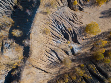 Fancy and unusual autumn aerial landscape of Romantsev mountains wih blue lakes, yellow trees and mud erosion looks like alien surface of Mars. Russia. Tula national park