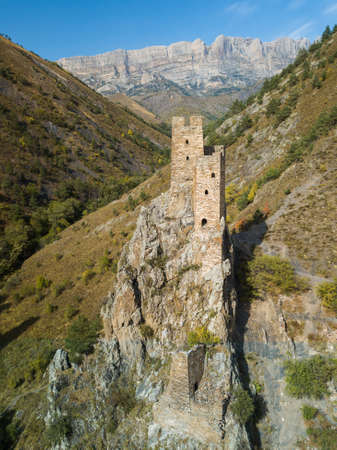 Aerial view of medieval ancient stone battle tower complex in the mountains of Ingushetia, Russia Фото со стока