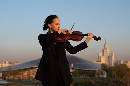 Beautiful female professional violinist playing outdoors on a violin in a black suit.