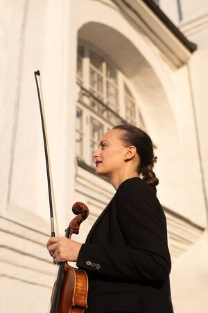 Beautiful female professional violinist playing outdoors on a violin on white stone building as background.