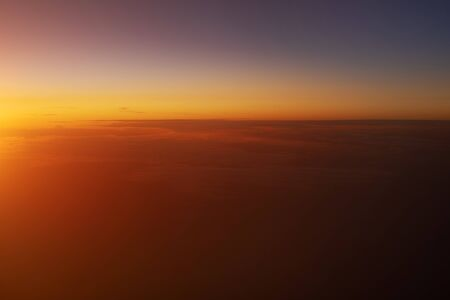 Beautiful view of sunset sky above clouds from airplane. 免版税图像