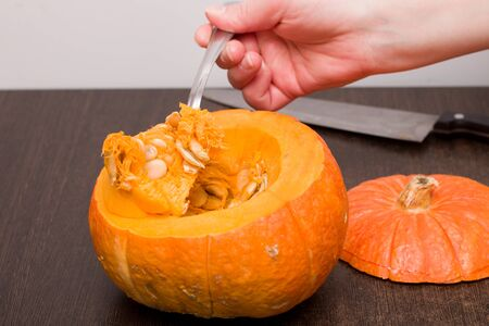 woomen hand with spoon pulls out thu pumpkin brush with seends iron knife on the background