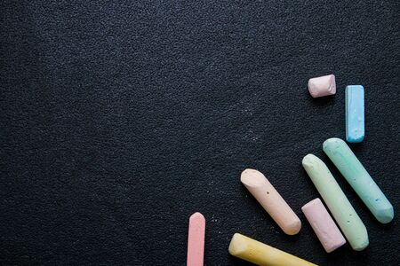 several colored crayons on a black background, chalk, draw on the asphalt with chalk, copy space, top view