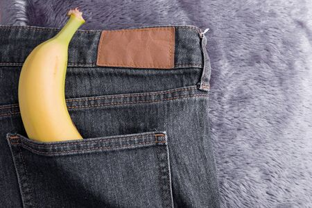 banana in the back pocket of grey jeans top view yellow fur background
