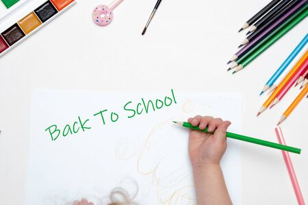 child hand holds a green pencil draws writes on a white piece of paper white background top view place copy back to school lettering paint pencils brush pink pen with donut Standard-Bild