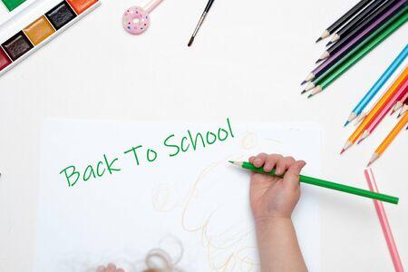 La main de l'enfant tient un crayon vert dessine écrit sur une feuille de papier blanc fond blanc vue de dessus place copie retour à l'école lettrage crayons de peinture pinceau stylo rose avec beignet Banque d'images