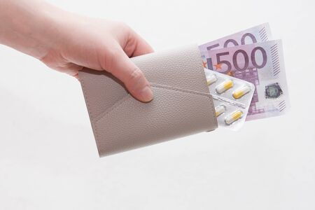 female hand holds a wallet with yellow capsule pills and euro notes, white background Stock Photo