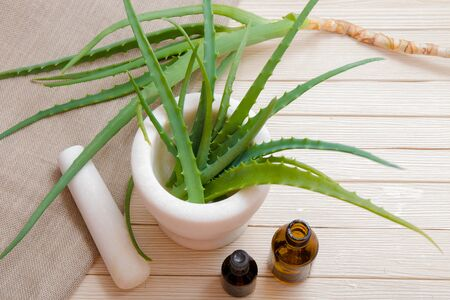 natural cosmetics, aloe in a white stone mortar, wooden plank table, beige background, linen fabric, small bottles of dark glass,
