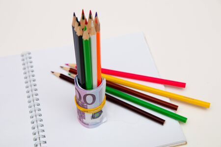 colored pencils wrapped in euro note stand on a white notebook on a white table bright spot copy