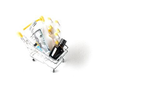 pharmacy,medicines and dollars in a shopping trolley and mercury thermometer on a white background copy space