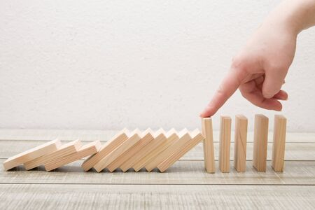 hand finger stops falling wooden dominoes, white background, domino principle, business concept