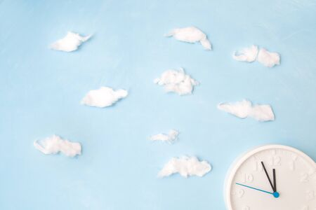 white clock on a blue background with clouds of cotton wool, the concept of time and its waste, place of copy, dial, 11 hours 55 minutes