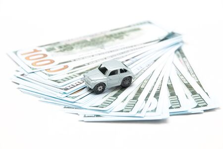 old dirty miniature car toy on a bundle of 100 dollar bills, buying a used car concept, retro car