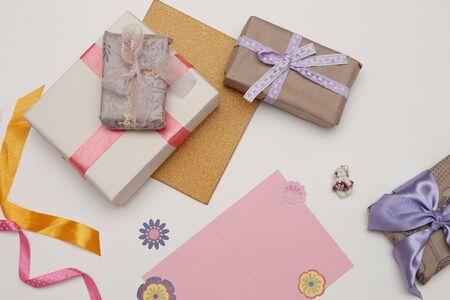 粉色卡片纸和美丽的礼物在白色的背景感恩节,生日,母亲节,拷贝空间,纸花,丝带和蝴蝶结装饰
