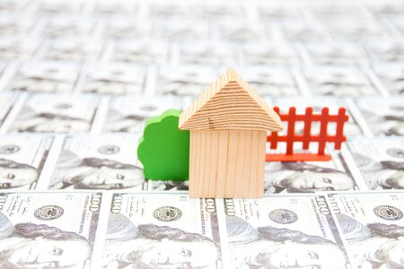 wooden toy house, bush and fence on the background of 100 dollar bills laid out on a table, real estate country house concept