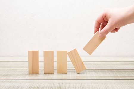 hand put wooden dominoes in a row white background, frontal feed, rectangles for your inscription 5 letters Banque d'images